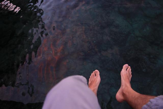 Feet in sunset reflection on water, Iboih, Sabang, Pulau Weh