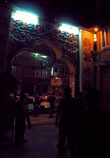 Night's neon lights over Boudha's front gate, taxis waiting for fares, decorated truck, 8 auspicious symbols, wish fullfiling jewels, zephrs, apartment building and restaurant beyond, Boudha, Kathmandu, Nepal, 1990