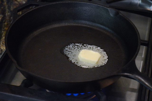 Butter melting in a cast iron skillet on the stove.