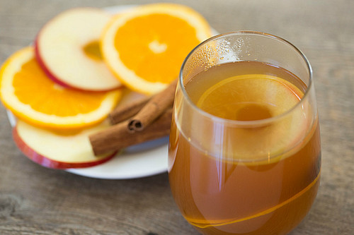 Rum punch with apple cider, apples, oranges, ginger and cinnamon sticks