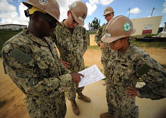 Seabees from Naval Mobile Construction Battalion (NMCB) 3 and NMCB 5's engineering office discuss the construction plans for one of four ongoing construction projects across Okinawa, Japan, during their turnover. (U.S. Navy photo by Mass Communication Specialist 1st Class Chris Fahey)