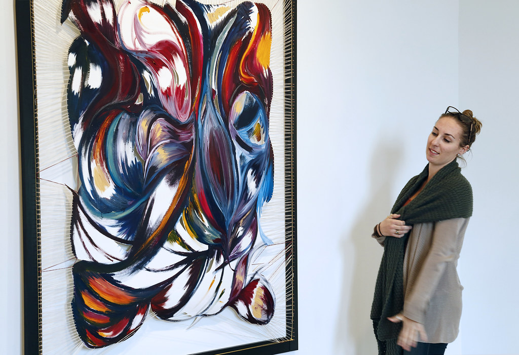 Kate Huffman (M.F.A. '18) with her painting in the Experimental Gallery.