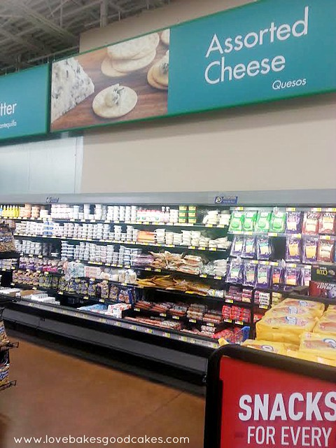 Grocery store isle with assorted cheese products on the shelf.