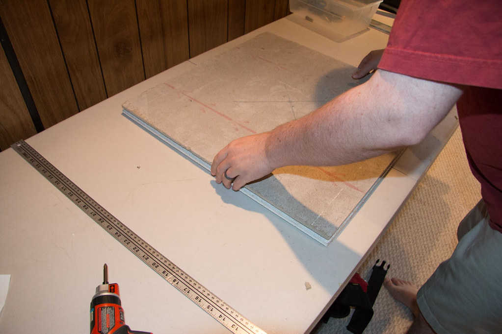 Using template to cut holes in ceiling tiles for recessed lighting installation