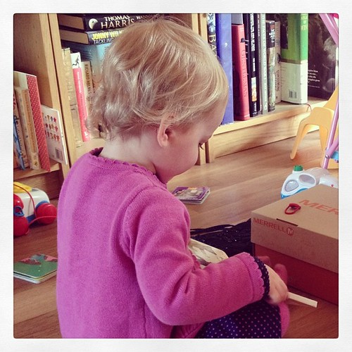Small niece looking at books. I love the way her hair curls at the back of her head. #poppet