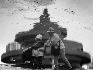 Wind Of May képe. qingdaoshi shandongsheng chine cn canon eos 100d 50mm asia china urban city qingdao street people asian chinese outdoor outside bw bnw black white blackandwhite water reflection chair handy old grandma cold hat push pushing roll rolling bag coat glasses wind movement moving puddle rain monument landmark dirts dirty team together power help circle wheel