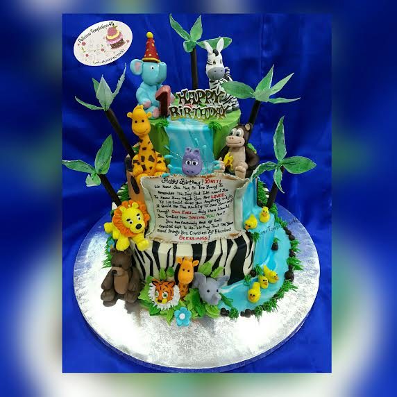 A chocolate cake frosted with coloured chocolate ganache.. with hand crafted fondant animals and wafer paper tress by Delicious Temptations 4U