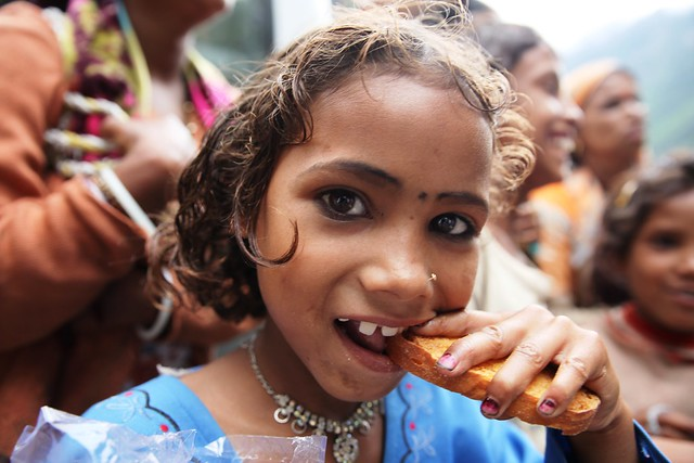 A girl eats a biscuit as part of relief given by charity Save the Children in Pandukeshwar, 21 km from Joshimath on July 14, 2013. Floods and landslides, caused by heavy rains, devastated the Indian state on Uttarakhand on June 16 and 17, leaving tens of thousands of villagers cut off from main roads and in need of basic food and other items. Credit: Nita Bhalla/Thomson Reuters Foundation.