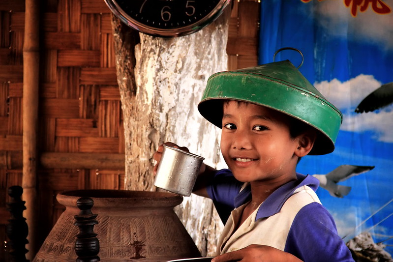 A Burmese Child Drinks A Cup Of Water