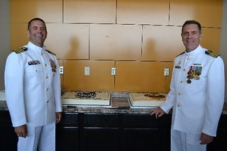 Capt. Timothy Wendt and Capt. William Drelling pose for a photo in front of a cake at Coast Guard Sector Lower Mississippi River, June 20, 2014. Capt. Wendt relieved Capt. Drelling as commander of Coast Guard Sector Lower Mississippi River in an official change-of-command ceremony.