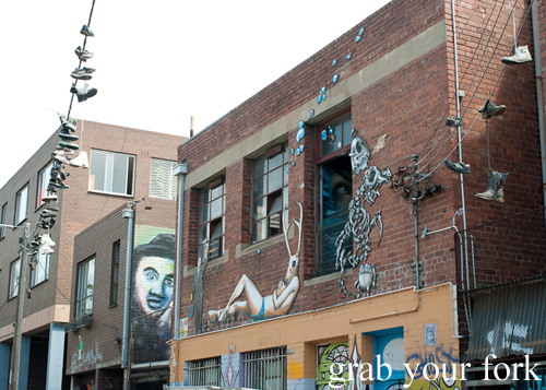 Graffiti murals and sneakers on power lines in Fitzroy, Melbourne