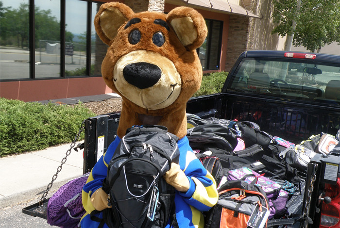 Del Norte Credit Union's Baxter Bear takes a moment to pose with some of the backpacks filled with school supplies that will help students start their school year off right