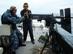 Chief Culinary Specialist Morio Hall and Gunner's Mate 1st Class Clarence Hall take part in a gunnery exercise aboard the littoral combat ship USS Freedom (LCS 1) in the South China Sea, Aug. 11. (U.S. Navy photo by Mass Communication Specialist 3rd Class Karolina A. Oseguera)