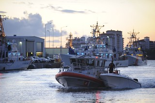 A Coast Guard Station Fort Lauderdale Response Boat -- Medium crew tows a vessel that capsized seven nautical miles east of Government Cut to Coast Guard Station Miami Beach, Fla., Oct. 16, 2013. The capsized vessel resulted in 11 people being rescued by the Coast Guard and four deaths. U.S. Coast Guard photo by Petty Officer 3rd Class Jon-Paul Rios.