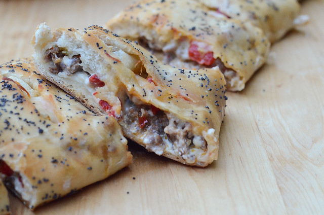 Slices of Italian Sausage Appetizer Bread on a wood board.