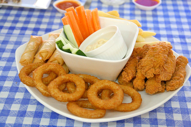 Snack platter of chicken tenders, onion rings, spring rolls and fries