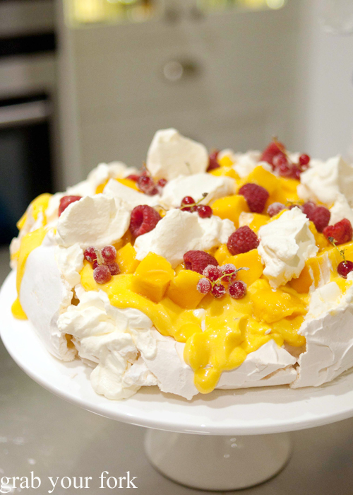 Homemade pavlova with homemade passionfruit curd, mango, raspberries and redcurrants