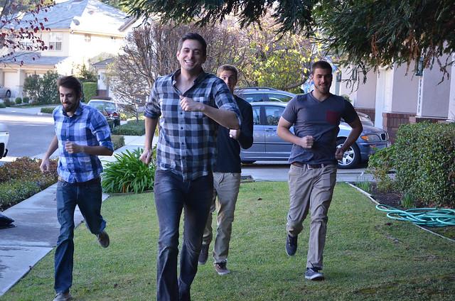Four young men run across grass towards the camera.