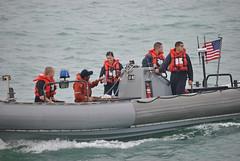 Lt. j.g. Katherine Miyamasu, center, provides water to a rescued Filipino mariner in the Singapore Strait, Jan. 18. (U.S. Navy photo)