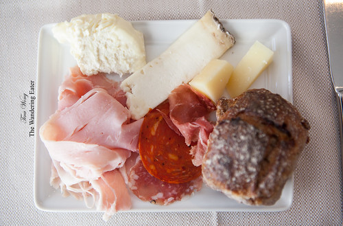 Plate of cheeses and charcuterie with a cranberry pecan roll