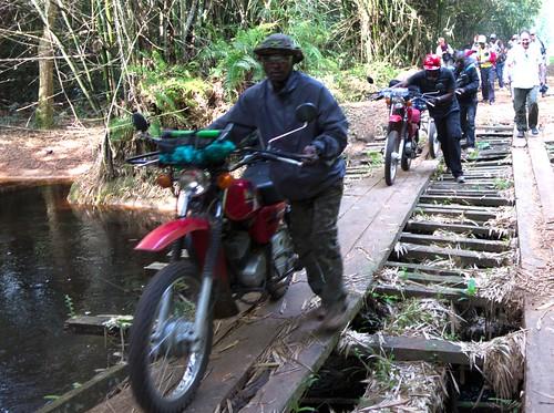 pushing bikes over flimsy bridge