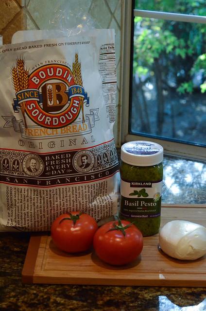 Boudin Sourdough Bread, tomatoes, pesto, and mozzarella cheese on a cutting board.