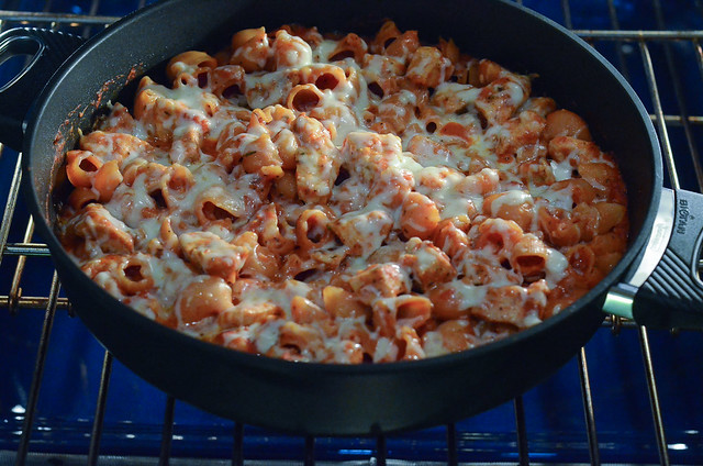 Pasta and chicken with melted cheese in a skillet.