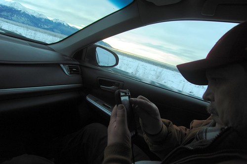 Ward Lane checking his smart phone as we drive Seward Highway along Turnagain Arm in the winter towards Kenai Pennisula, south east of Anchorage, Alaska, USA by Wonderlane