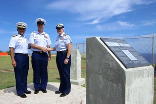 Left to right: Cmdr. Flip Capistrano, Air Station Borinquen executive officer; Petty Officer 1st Class Samuel Allen, aviation maintenance technician, and Capt. Patricia McFetridge, Air Station Borinquen commanding officer, stand on top of an artillery mount following the revealing of a War World II memorial. The memorial was dedicated in honor of the military service members who manned the 155 mm rifled artillery batteries established to protect the island and Mona Passage from possible Nazi German Naval surface ship incursions, during a ceremony at the installation's park grounds May 23, 2014, in Aguadilla, Puerto Rico. (Photo by Petty Officer 2nd Class Arturo Guerrero, avionics electrical technician)