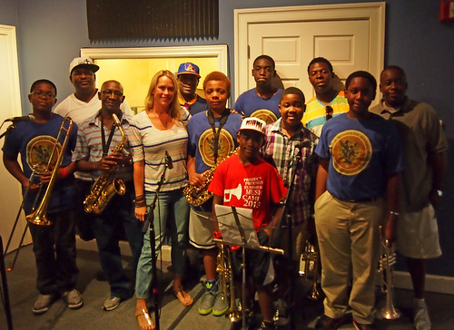 Roots of Music: Theron Sanchez, Jeffrey Hills Sr, Darryl Adams, WWOZ Director of Major Giving Lauren Del Rio, Tanio Hingle, Demetris Chamblis, Jeffrey Hills Jr (front), Dante Scott, Ian Green, Kerry Hunter, Gregory Cyres, Lawrence Rawlins