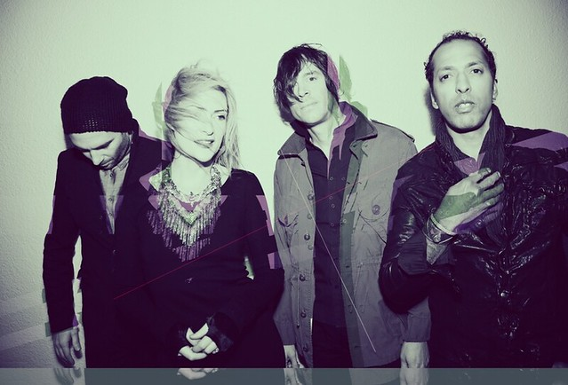 Emily Haines, a white woman with blonde hair, in a distorted photo of her band, which features three guys.
