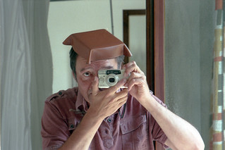 reflected self-portrait with Samsung Vega 140s camera and leather hat