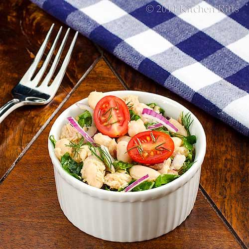White Bean, Tuna, and Swiss Chard Salad with cherry tomato garnish