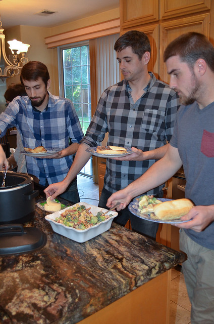 A group of men serving up plates of food in a kitchen.
