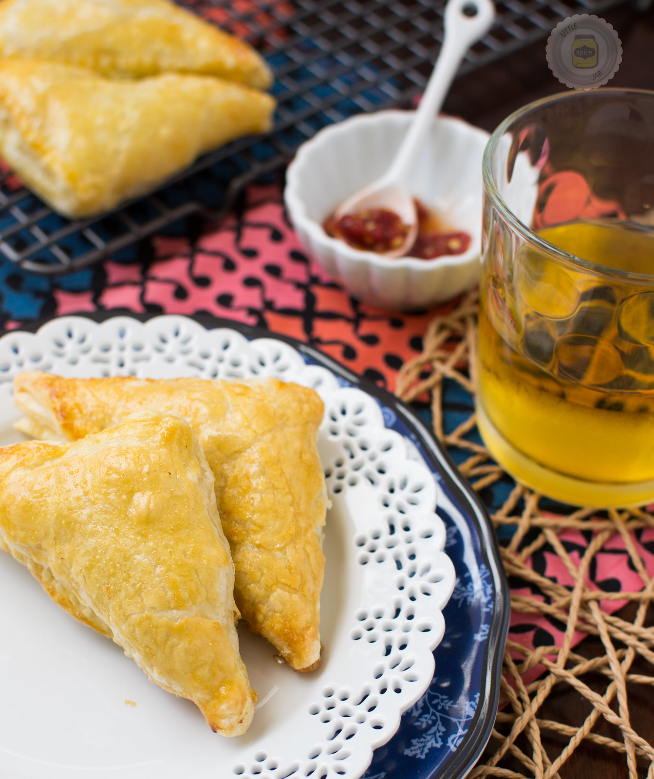 stacked plates with chicken puff pastry triangles, glass with drink, and chili garlic sauce in bowl with spoon