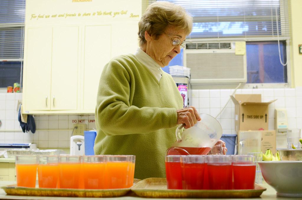 volunteer pours juice