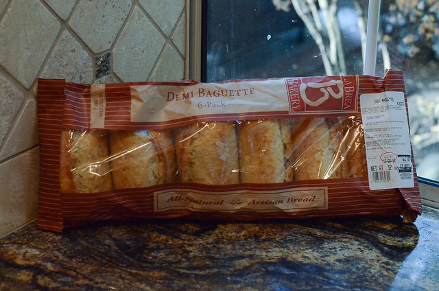 A bag filled with small baguettes.