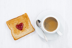 toast in heart shape with fruit jam and cup of cof…
