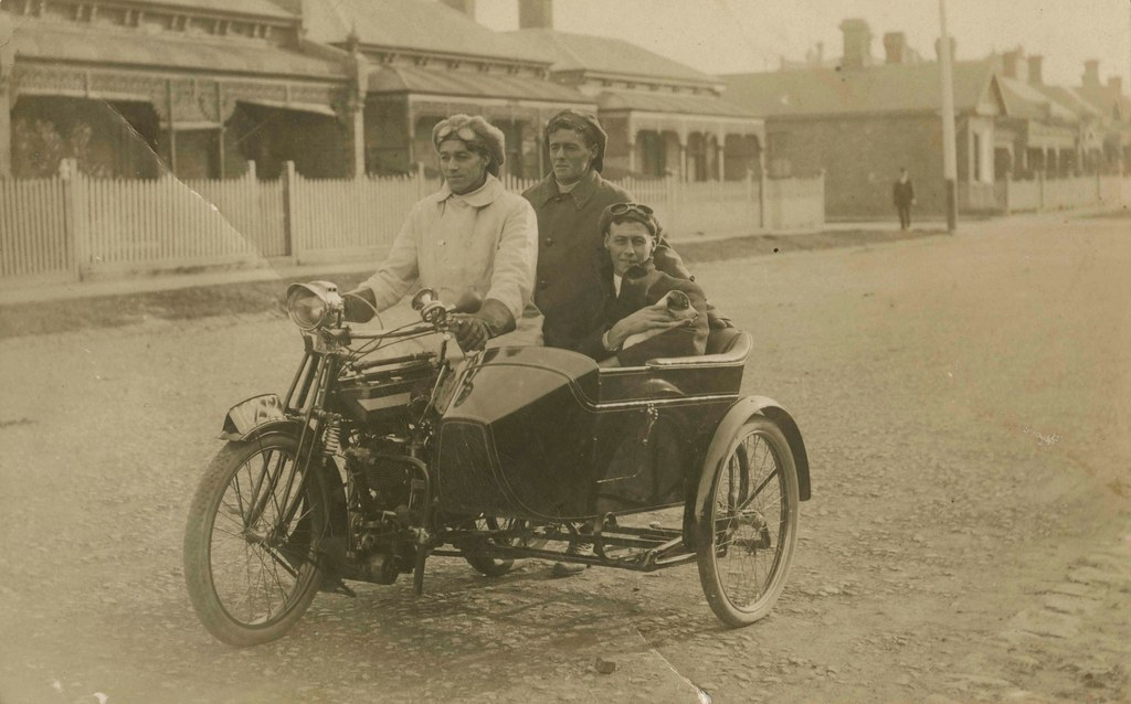 Photographic postcard of three men and a dog in a motorcycle and sidecar