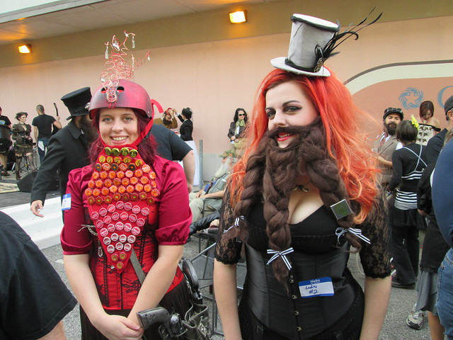Two female steampunk cosplayers wearing elaborate beards and fancy women's clothes