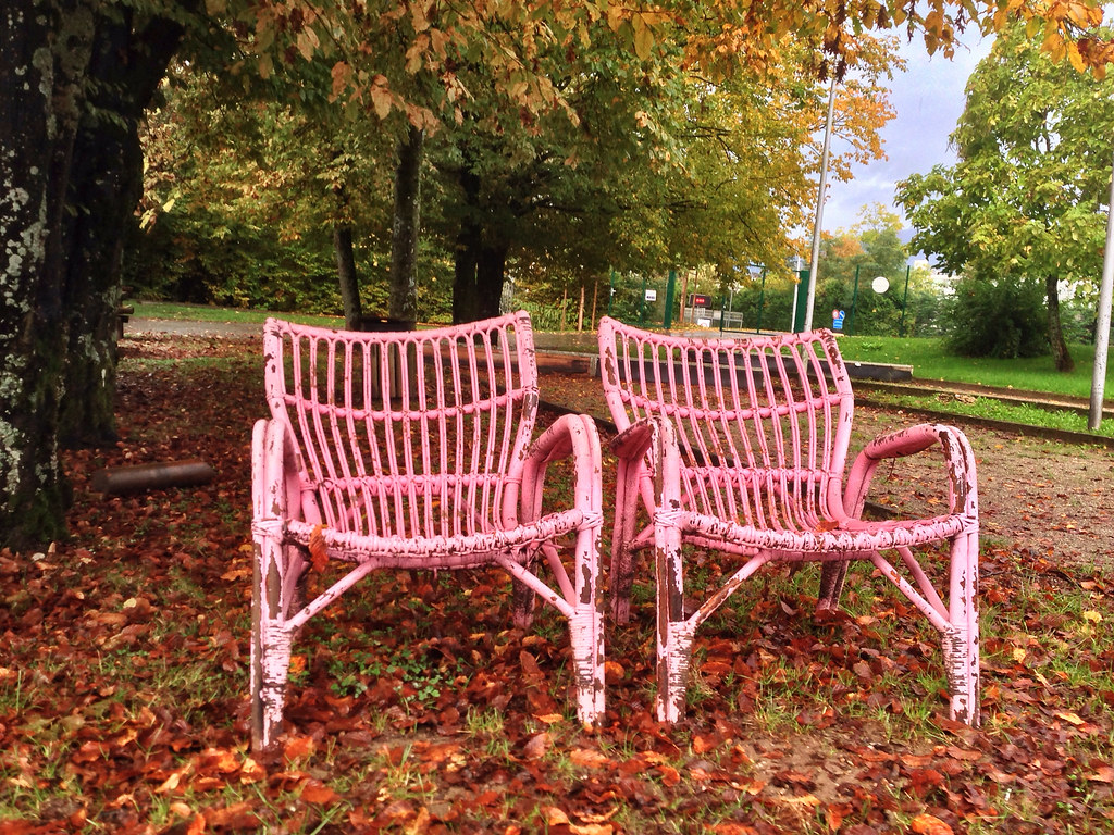 Pink chairs rotting in the autumn weather