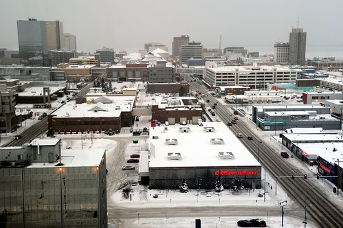 Snowy white rooftops, downtown Anchorage mid-winter, 5th Ave to the right, hotels, oil companies, parking buildings, 3 sky bridges, Office Depot foreground, facing west, view from 15 stories up, Sheraton Anchorage Hotel, Anchorage, Alaska, USA