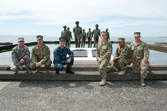 Sailors and an Airman, all part of the Pacific Partnership 2014 mission team, pause for a photo at the Leyete Landing Memorial in Tacloban, Philippines. (U.S. Navy/MCC Greg Badger)