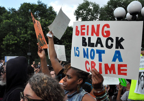 Woman with sign: Being black is not a crime.
