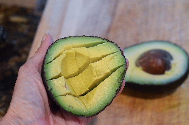 Half on an avocado is sliced into cubes.