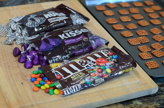 Bags of M&M's and Hershey's Kisses on a wood cutting board.