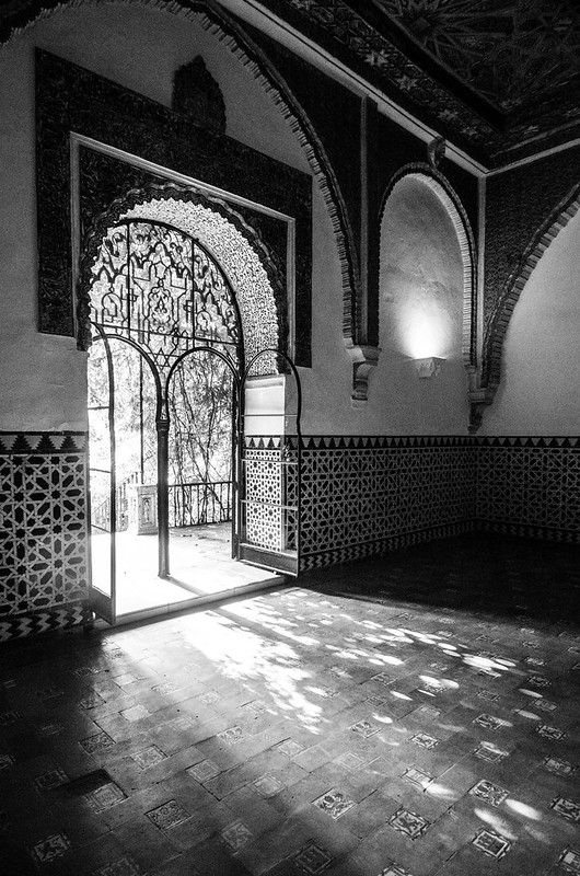 Dappled light flows through ornate windows at the Royal Palace in Sevilla, Spain.