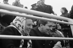 Prinses Beatrix en Prins Claus als toeschouwers op de tribune bij de schaatswedstrijden /Princess Beatrix and Prince Claus as spectators in the stands at the women's speed skating
