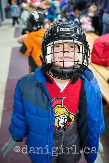 小男孩滑冰课曲棍球齿轮的照片