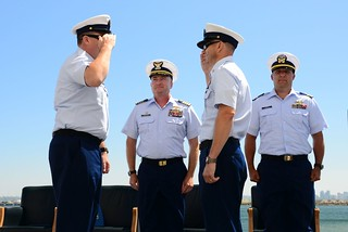 Capt. Sean Mahoney, commander of Coast Guard Sector San Diego, and Lt. Cmdr. Jeff Parks, the chaplain for Sector, look on as Master Chief Petty Officers John Bowen (left), and Chris Swiatek swap command during a change of command ceremony at Naval Base Point Loma, July 10, 2014. Swiatek, the Petrel outgoing officer in charge, took over for Bowen as the officer in charge of the Sea Otter and Bowen took the reigns from Swiatek for the Petrel. U.S. Coast Guard photo by Petty Officer 3rd Class Connie Terrell.